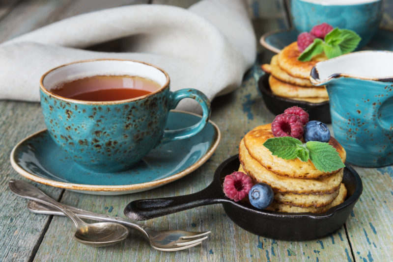 Two small cast iron frypans with stacks of pancakes, next to a mug of tea