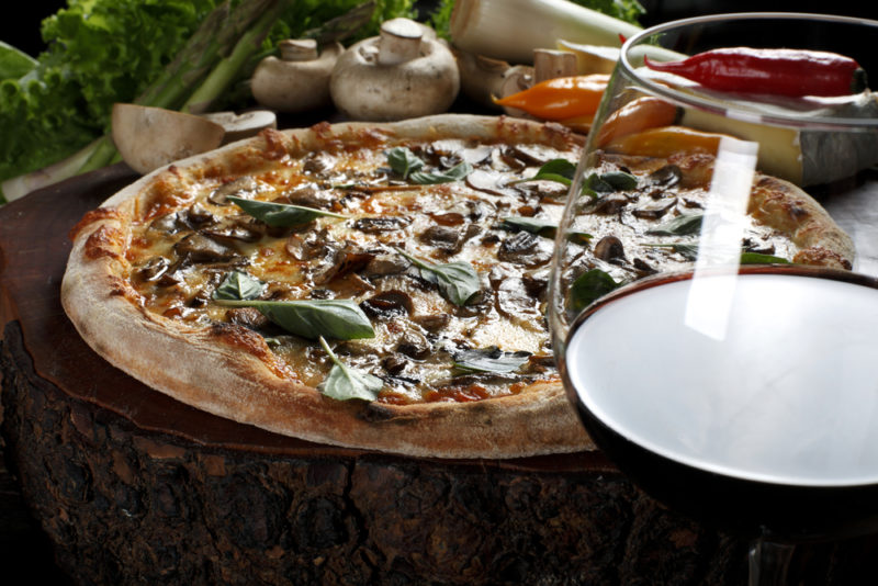 A glass of red wine in the foreground with a mushroom pizza behind it and various fresh ingredients