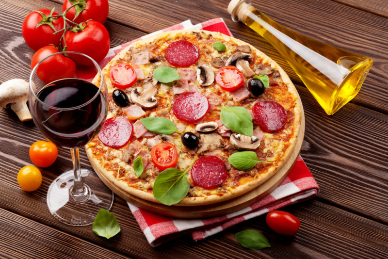 A fresh pepperoni pizza on a table with olive oil, wine, and tomatoes