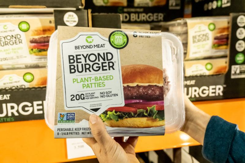 A person holding up a Beyond Burger container in the grocery store, with more behind them