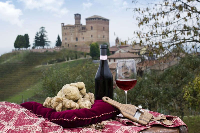 A picnic of truffles and red wine, with an old building in the background