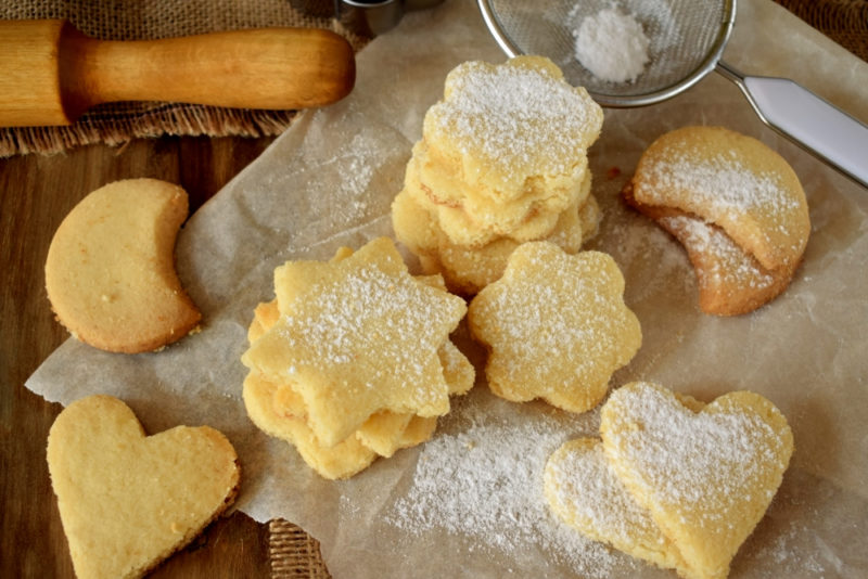 A piece of parchment paper with shortbread in different shapes, some of which are covered in sugar