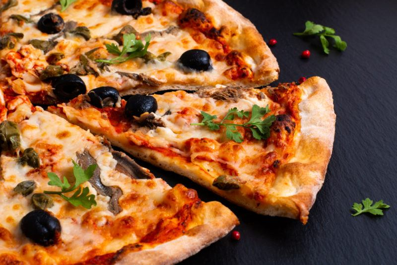 A black tabletop with a pizza that has anchovies and olives