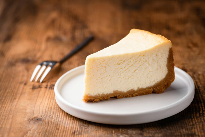 A plain cheesecake on a white plate next to a fork