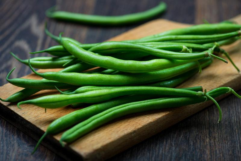 Fresh green beans on a wooden plank
