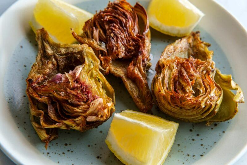 Three pieces of Jewish-style fried artichokes, with three lemon wedges on the same plate