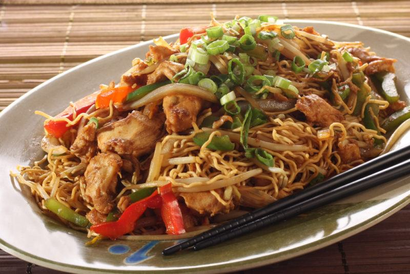 A brown dish of chow mein with chopsticks and some greenery