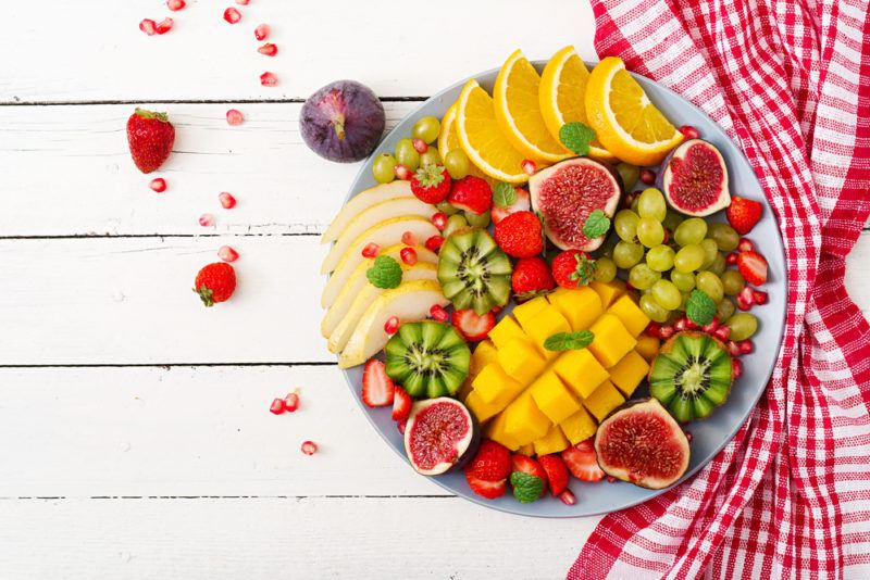 A plate of fresh tropical fruit on a wooden table