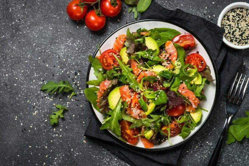 A large bowl of salad with avocados and fish