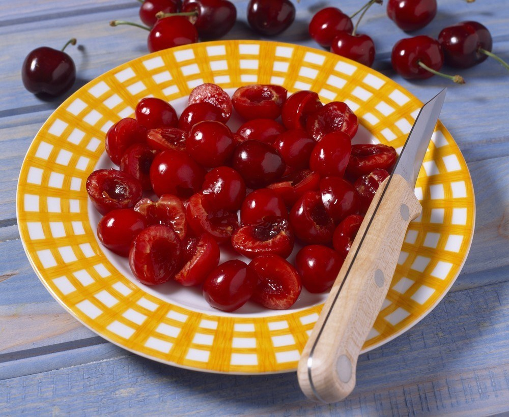 A yellow and white plate with cherries that have been cut in half