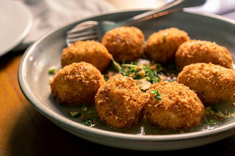 A small gray bowl filled with a circule of croquetas