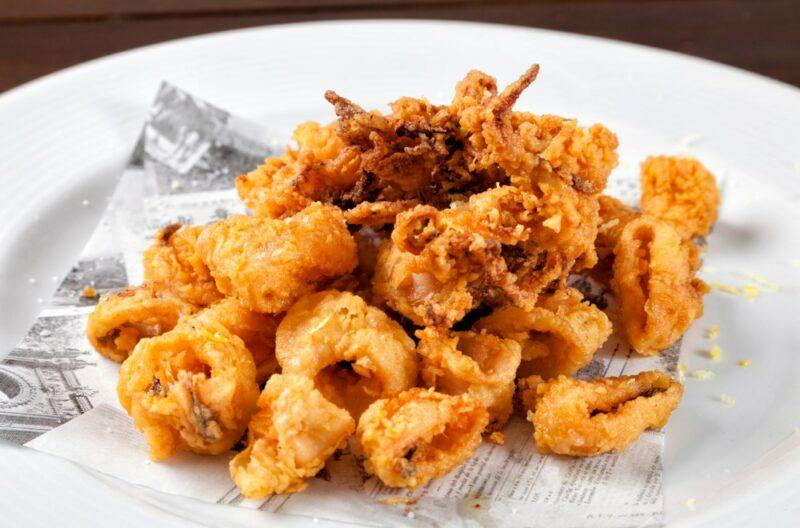 A white dish that contains various pieces of fried calamari