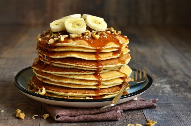 A plate with a large stack of pancakes with bananas on top