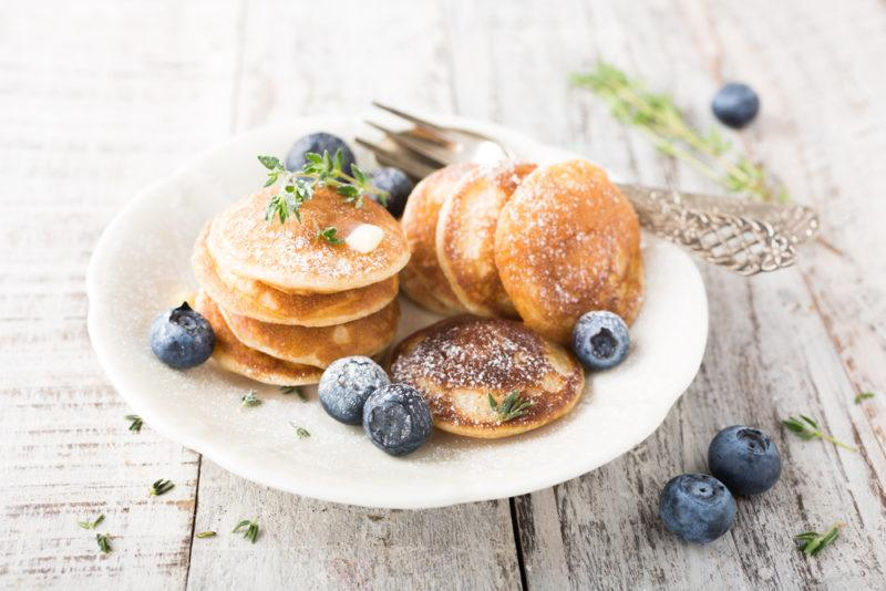 A white plate with small pancakes and blueberries