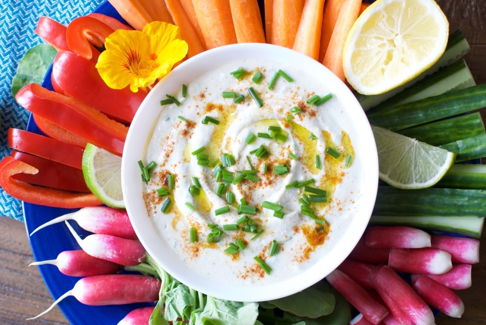 A large blue dish with cut veggies and a white bowl of dip
