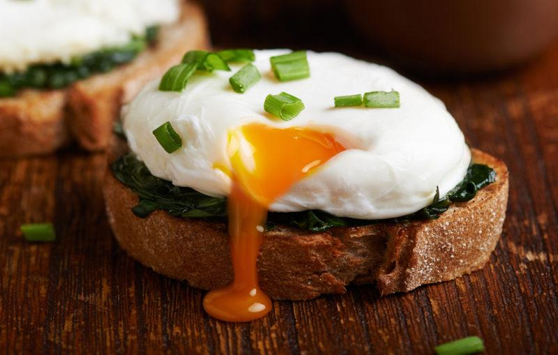 A perfect poached egg on a piece of sourdough toast with spinach