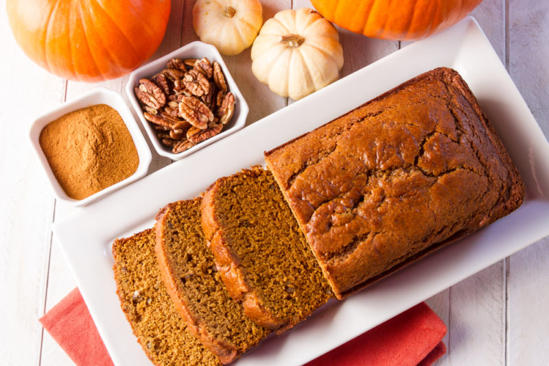 A white plate with a pumpkin loaf that has been sliced next to pumpkin spice and walnuts