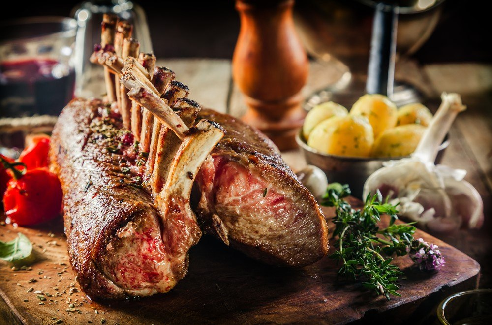 A rack of cooked lamb on a wooden board with other ingredients like potatoes and tomatoes