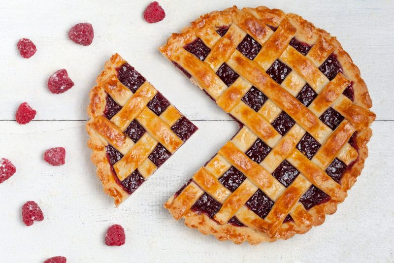 A raspberry and lemon pie with one piece that has been cut out of it and raspberries scattered around