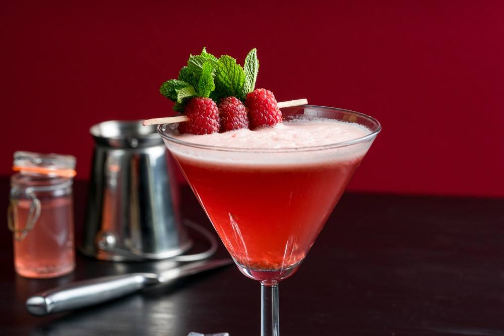 A raspbery martini in a cocktail glass with a pretty raspberry garnish
