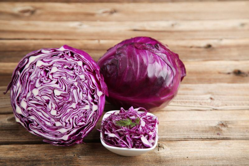 Half a red cabbage, a red cabbage and shredded cabbage in a small bowl