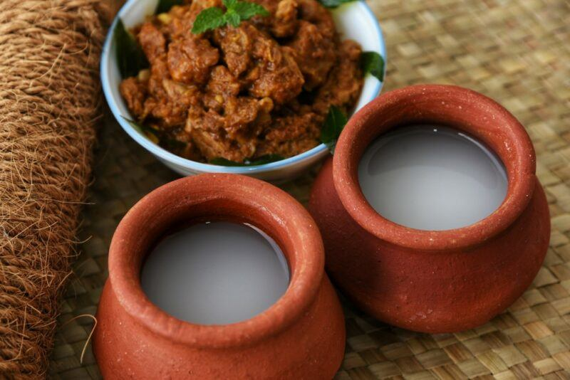 Two terracotta mugs with white Indian toddy, in front of a white bowl of curry