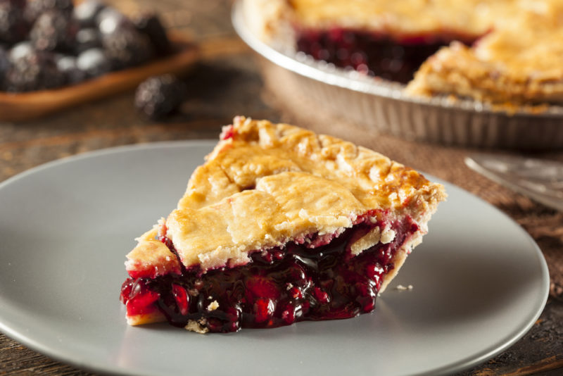 A gray plate with a piece of berry pie, with the rest of the pie in the background