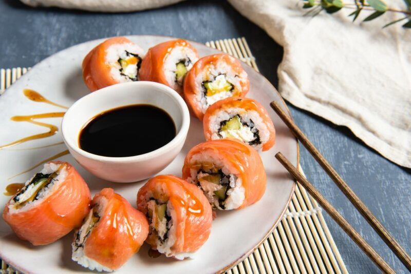 A white plate with sushi wrapped in salmon, around a bowl of soy sauce