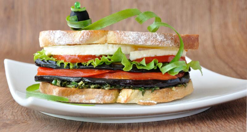 A white plate with an eggplant, cheese, lettuce and tomato sandwich