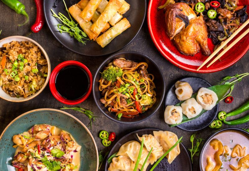 A black table with many small dishes of Chinese food