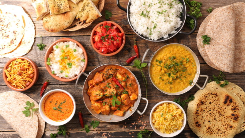 A selection of Indian curries on a table with rice and naan bread