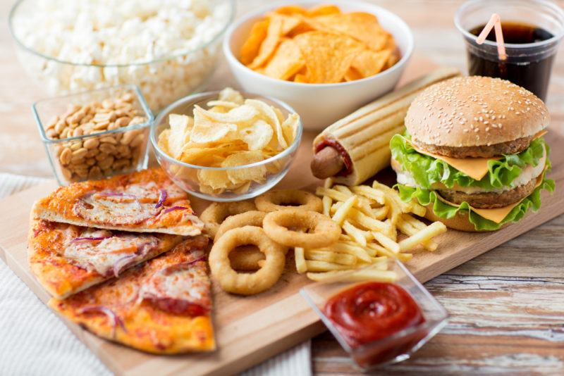 A selection of fast food, including burgers, fries, onion rings, and pizza