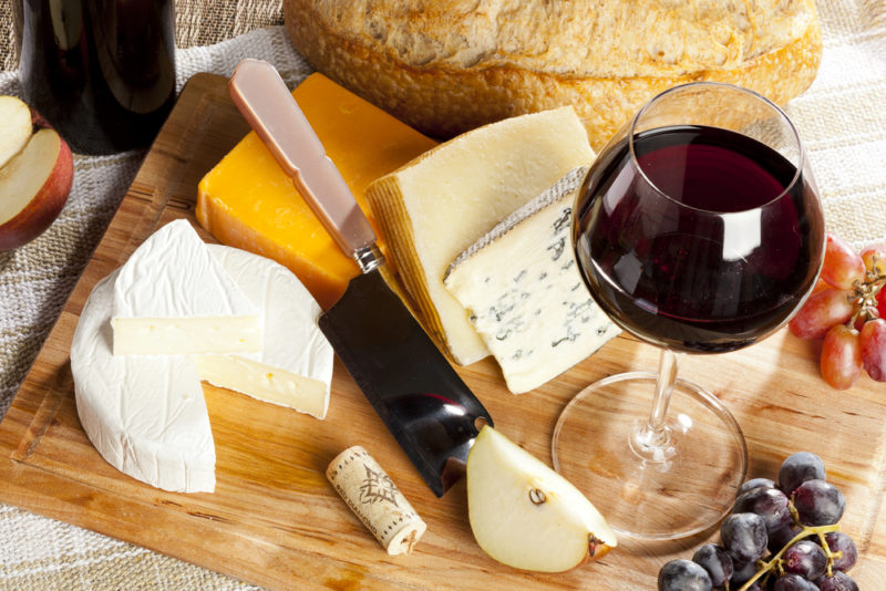 A wooden board with various cheeses, a knife, and a glass of red wine