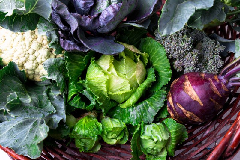A red basket filled with cruciferous vegetables, including cauliflower and cabbage