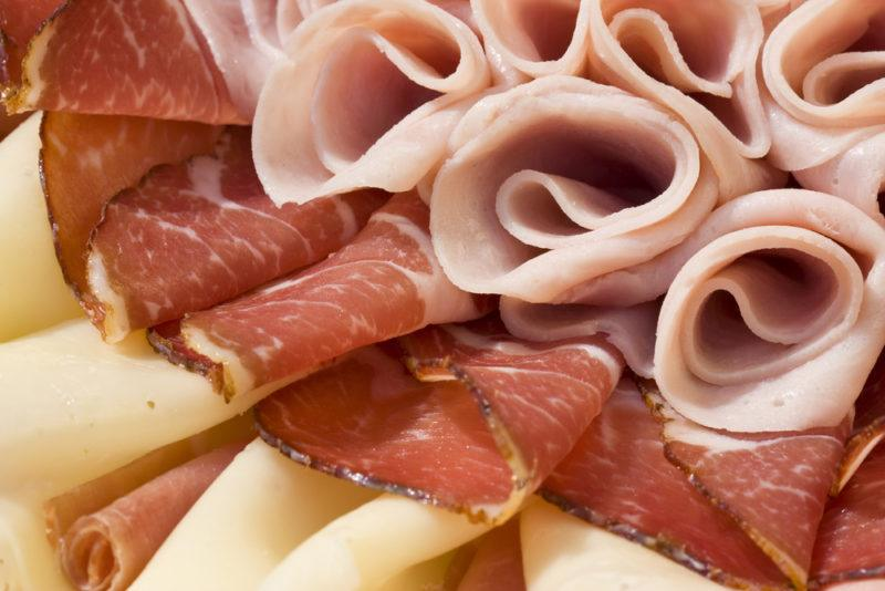 Various types of deli meat, some of which has been rolled