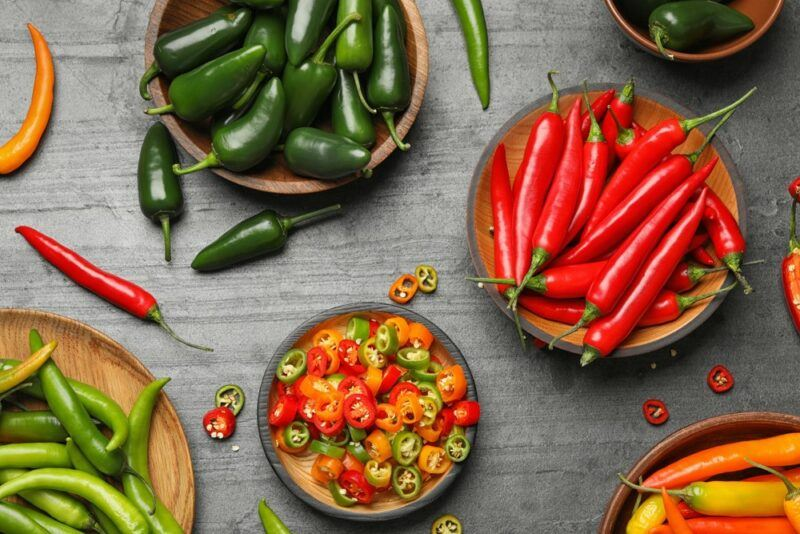 A gray table with a selection of hot peppers, including some red ones and various green peppers, along with a bowl of sliced hot peppers