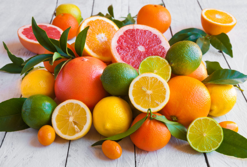 A selection of fresh citrus fruit on a white wooden table with grapefruit, lemons, and limes