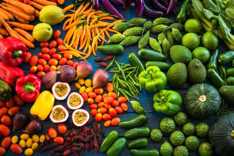 A selection of fresh fruit and vegetables on a table, in all colors