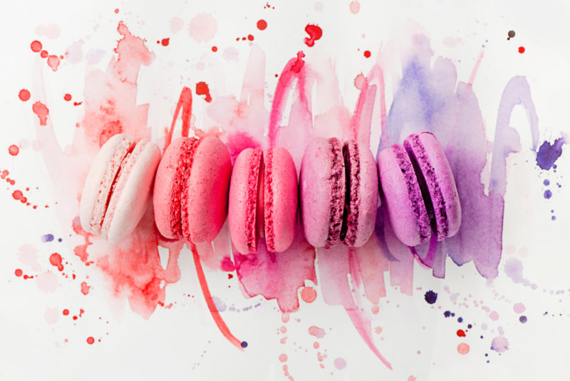 Five macarons in different colors with colored paint underneath them