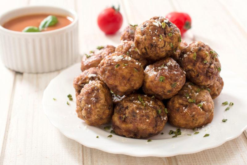 A white dish of meatballs piled high, with a dish of sauce in the background