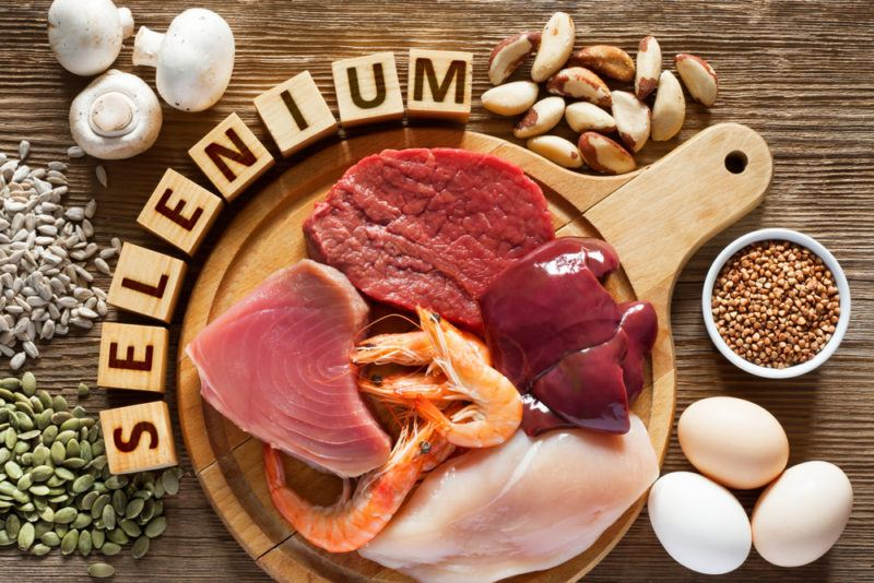 A brown wooden table with various selenium rich foods and the word selenium made from blocks