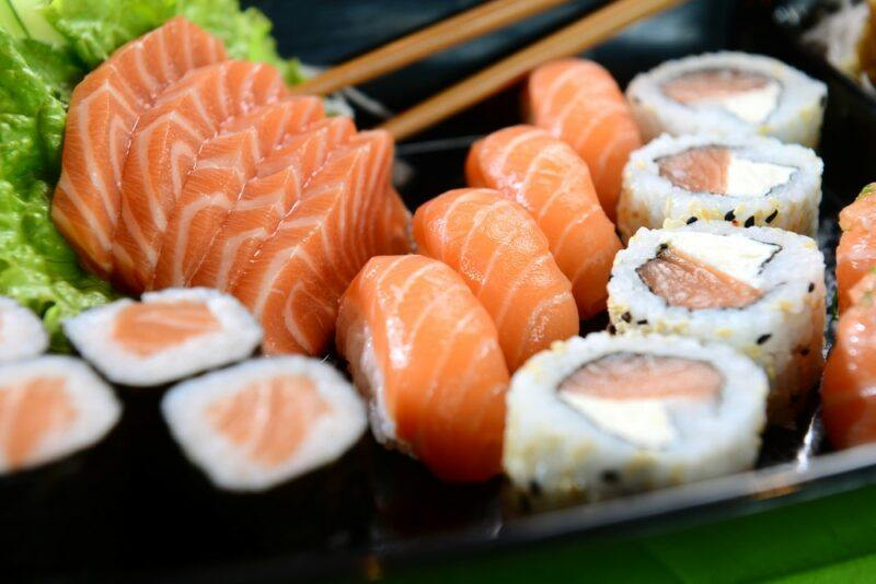 A plate with various types of salmon sushi and some chopsticks