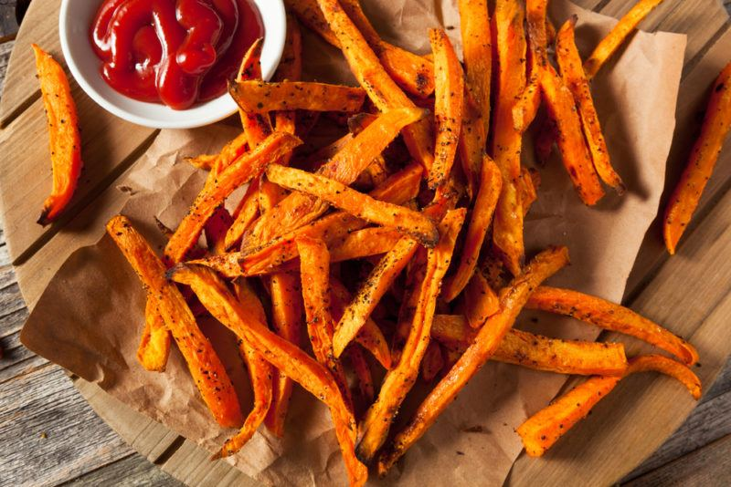 Many sweet potato fries on a piece of paper next to sauce