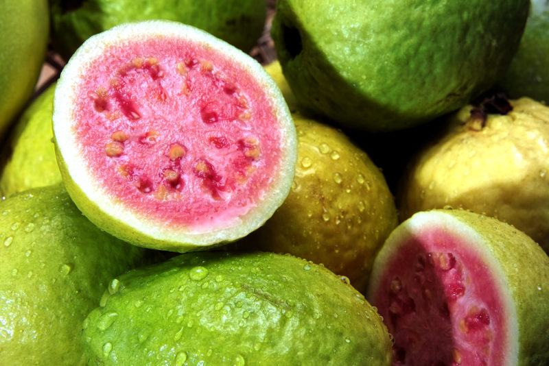 A selection of whole guava with one cut open revealing the pink interior