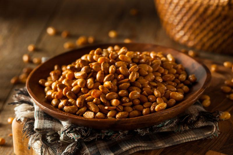 A shallow dish or bowl that contains roasted soybeans on a cloth