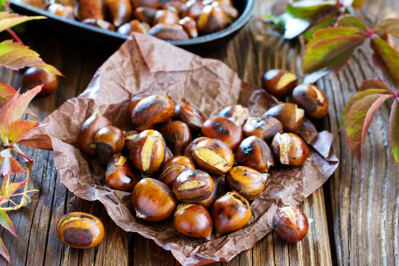 A sheet of crumpled paper with roasted chestnuts on a wooden table