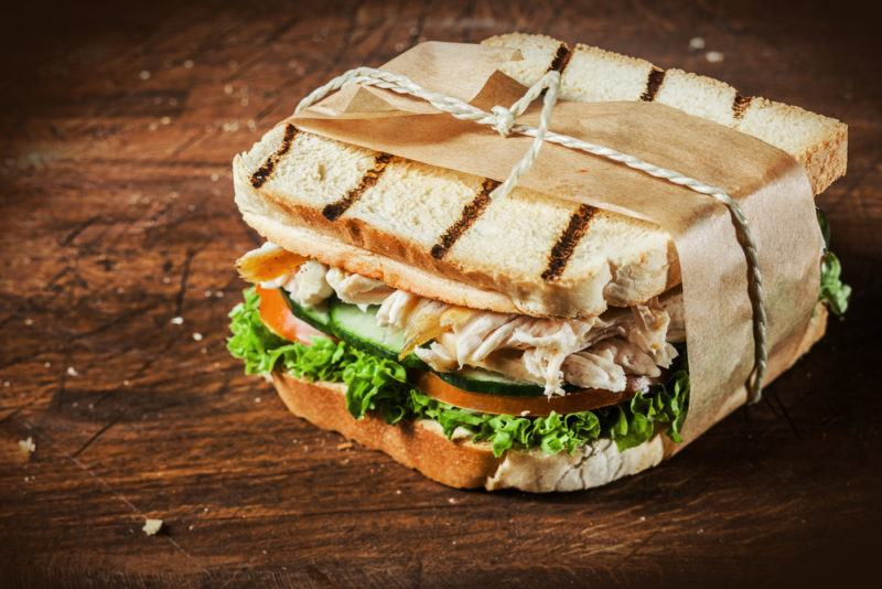 A toasted sandwich wrapped in paper on a wooden table that contains chicken and vegetables