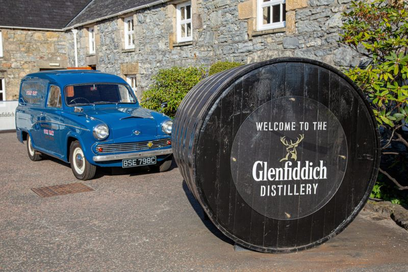 A sign for Glenfiddich whisky with a car behind it