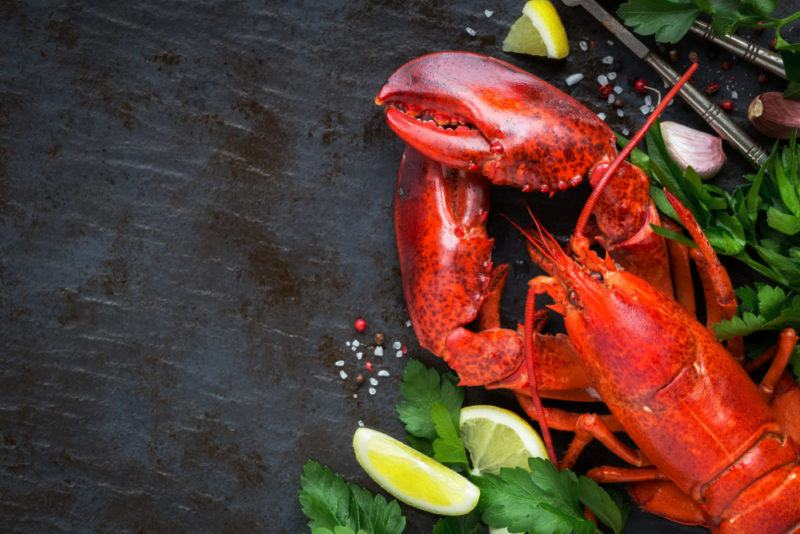 A lobster in the bottom right of the image with some greenery, seasoning, amd lemon wedges