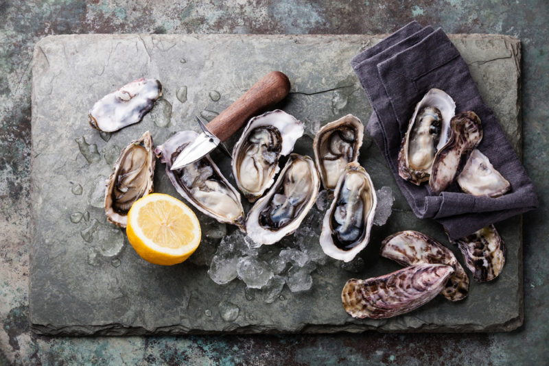 A slate board with fresh oysters and half of a lemon